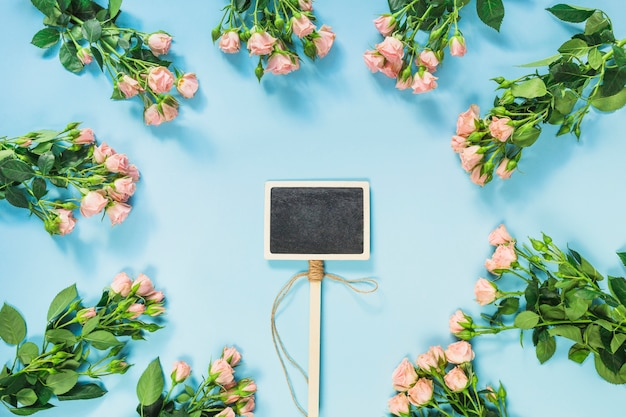 Blank blackboard label surrounded with bunch of pink roses on blue background