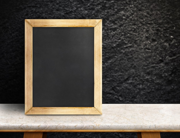 Blank blackboard on marble table at blurred rough black stone wall