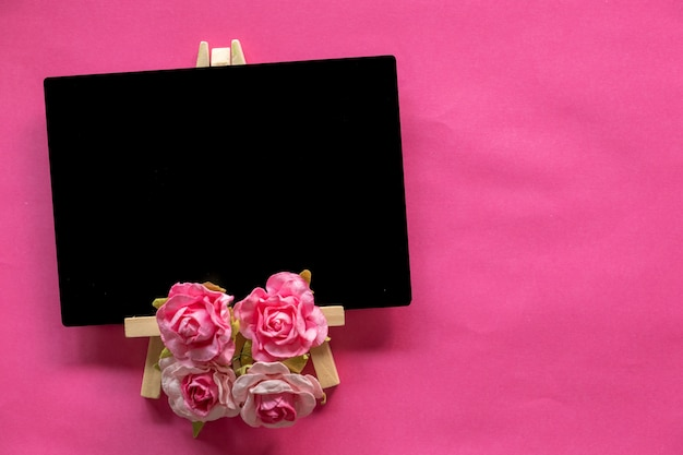 Blank blackboard and pink flower on pink background