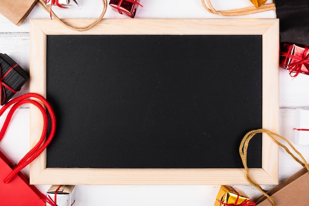 Blank blackboard surrounded by gift bags