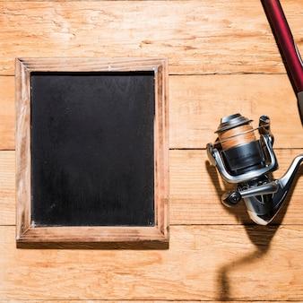 木製のテーブルの釣りリールと空白の黒板