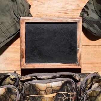 ズボンと空白の黒板。バッグとキャップの木製のテーブル