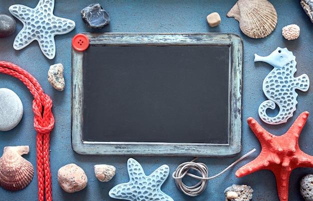 海の貝殻、ロープ、星の魚、スペースを持つ空白の黒板