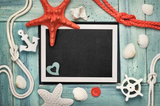 海の貝殻、石、ロープ、青い木製の背景、コピー領域の星の魚と空の黒板