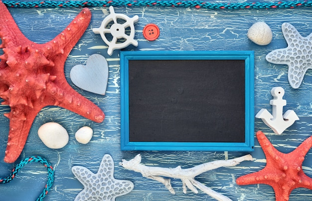 Blank blackboard with sea shells, stones, rope and star fish on