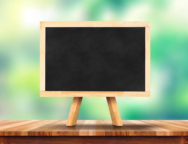 Blank blackboard on wood table with sun and blur green tree