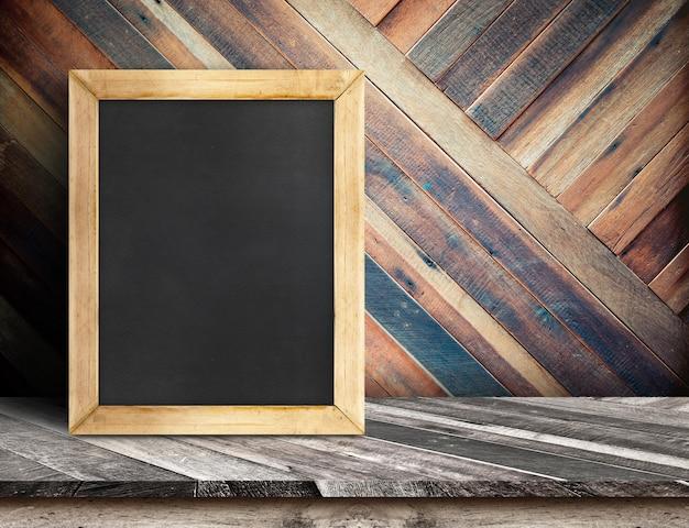 Blank blackboard on wooden table top at diagonal tropical wood wall