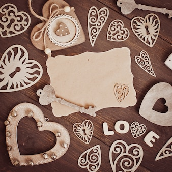 Blank blank and hearts on wooden background