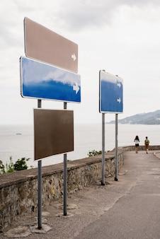 해변 도로를 따라 빈 파란색과 갈색 거리 표지판. 조롱