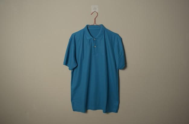 壁の背景の正面側面図でハンガーに空白の青いカジュアルなtシャツのモックアップ