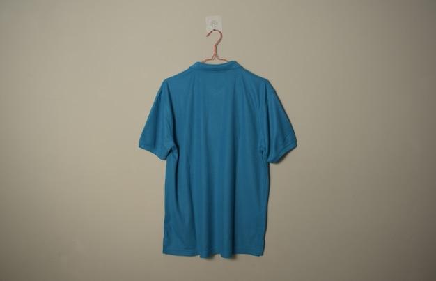 壁の背景の背面図でハンガーに空白の青いカジュアルなtシャツのモックアップ