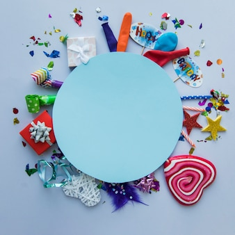 Blank blue circular frame over the birthday party items on background