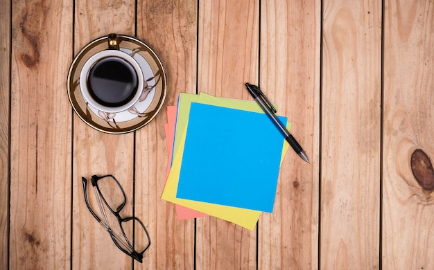 Blank blue paper for quotes with eyeglasses, coffee, and pen on top wooden table