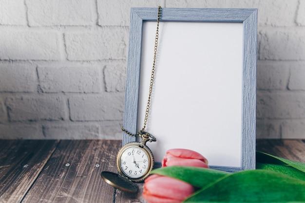 レンガの壁にヴィンテージの丸い時計とチューリップと空白の青いフォトフレーム