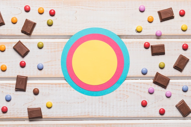 Blank blue; pink and yellow circular frame with confectionery on wooden desk