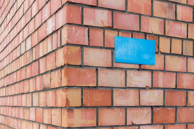 A blank blue plate is screwed to a brick wall. a sign at the corner of a brick building.