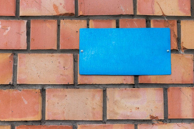A blank blue plate is screwed to a brick wall.