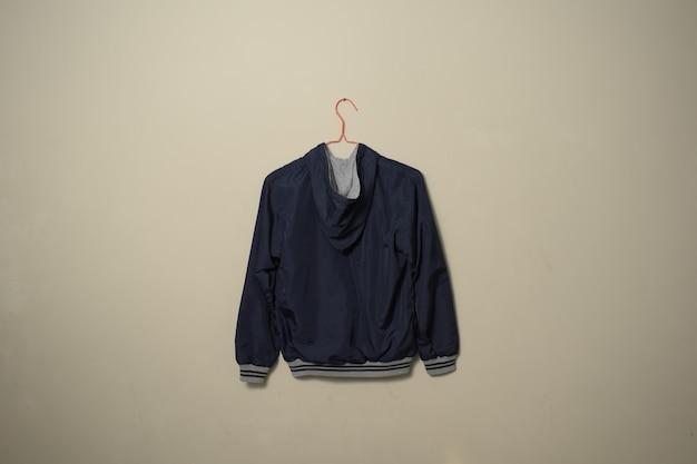Blank blue sport jacket mockup set hanging on hanger back side view on wall background