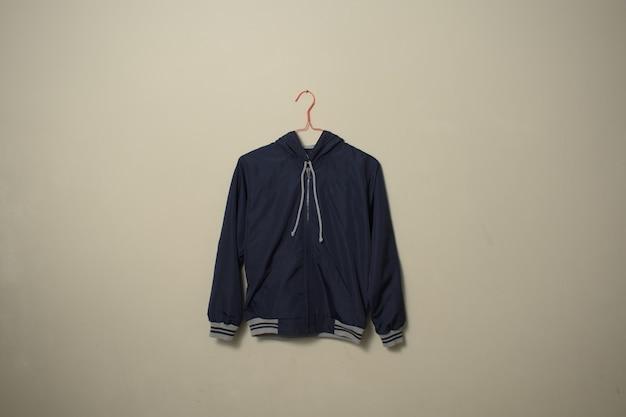 Blank blue sport jacket mockup set hanging on hanger front side view on wall background
