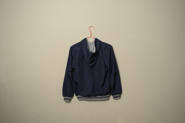 壁の背景にハンガーの裏側のビューにぶら下がっている空白の青いスポーツジャケットのモックアップセット
