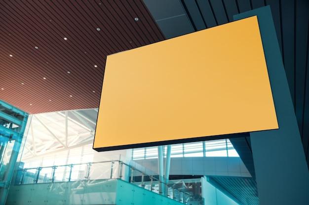 モックアップ用の空白のボード。空の黄色の水平ポスター。近代的な公共の建物の屋内シーン。含まれるクリッピングパス