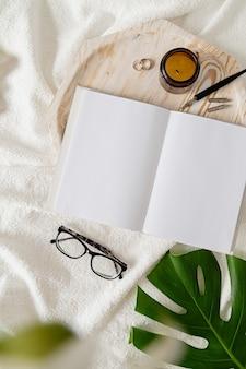 Пустая книга и свечи над деревянным подносом, очки, цветы и пальмовый лист над белой кроватью, плоская планировка