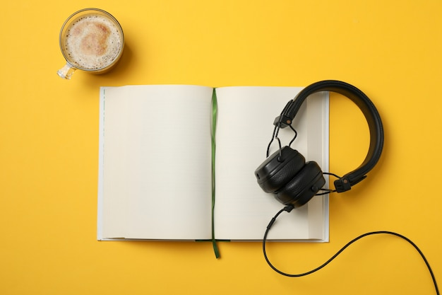 Blank book, headphones and cup of coffee on yellow space, top view