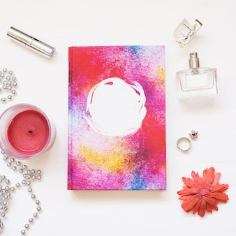 Blank  book isolated on white textured wood background with cute women's accessories