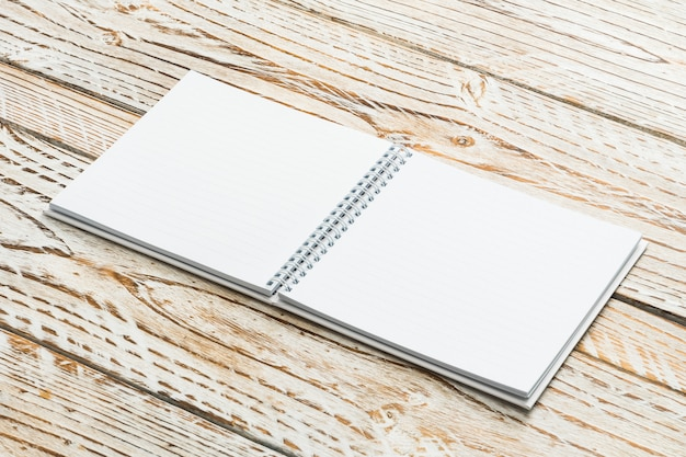 空白の本は木製の背景にモックアップ