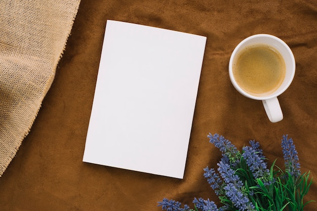 Blank book mockup with coffee and flowers