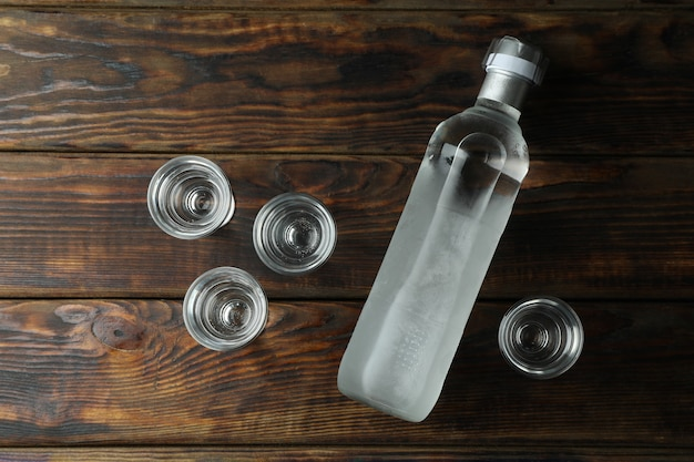 ウォッカの空白のボトルと木製のテーブルのショット