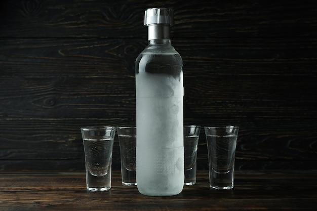 Пустая бутылка водки и рюмки на деревянном
