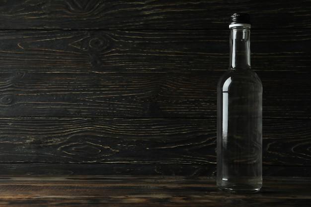 Blank bottle of vodka on wooden table