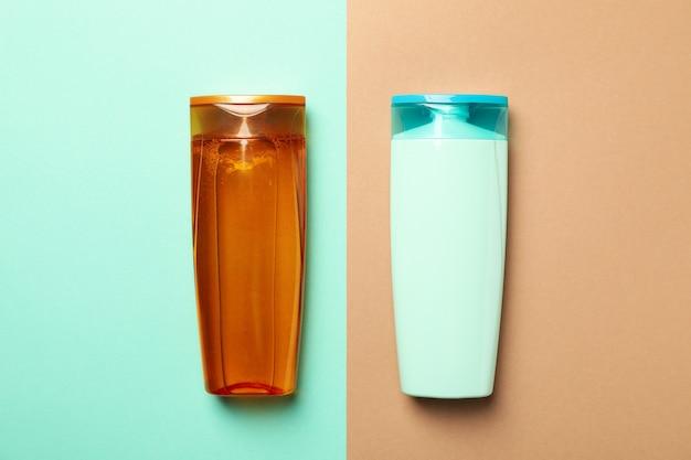 Пустые бутылки шампуня на двухцветном фоне, место для текста
