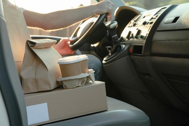 Пустая коробка, кофейные чашки, бумажные пакеты и курьер в машине