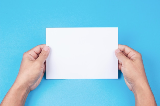 Blank brochure with blank in hand on blue background.