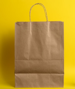 Blank brown craft package with handles for products and things on a yellow surface. refusal from plastic bags, zero waste