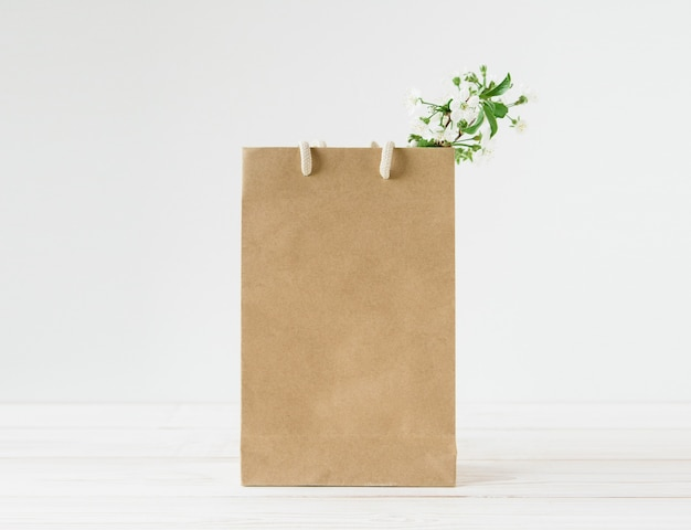 Blank of brown craft paper bag with handles.white background.fresh flowers.
