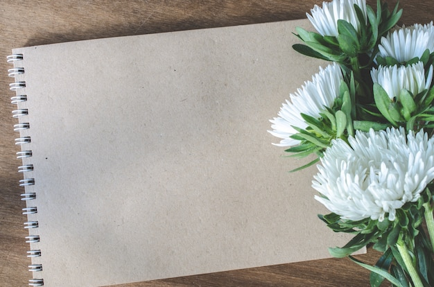 Blank brown notebook with autumn flowers.