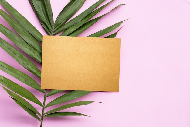 Blank brown paper on tropical palm leaves on pink surface