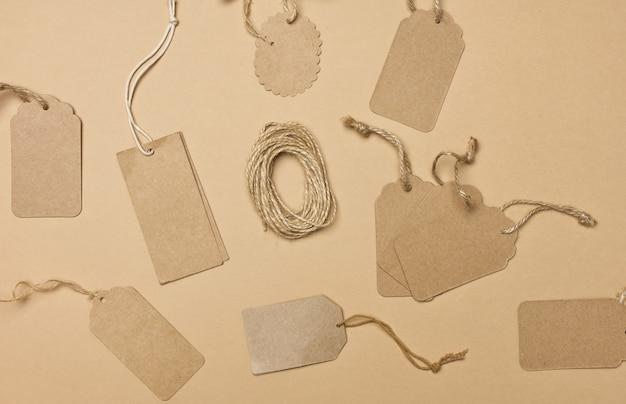 Пустая коричневая прямоугольная круглая бирка из коричневой бумаги на веревке, изолированной на белом фоне, шаблон для цены, скидки
