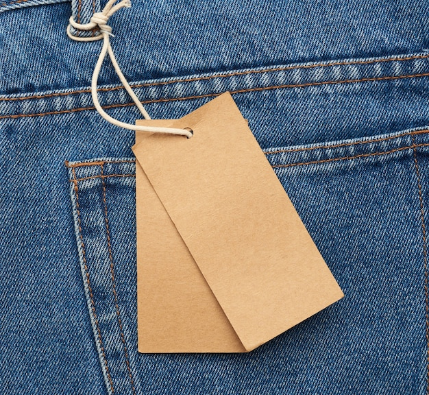 파란색 접힌 청바지 뒷주머니에 묶인 빈 갈색 직사각형 태그