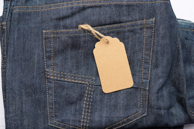 Пустая коричневая прямоугольная бирка, завязанная в заднем кармане синих сложенных джинсов