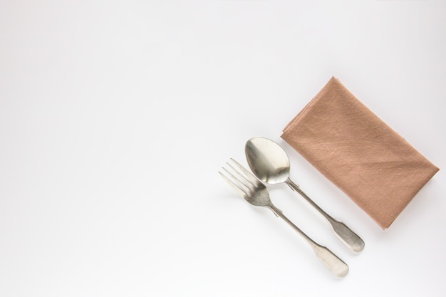 Blank brown restaurant napkin mockup with spoon and fork