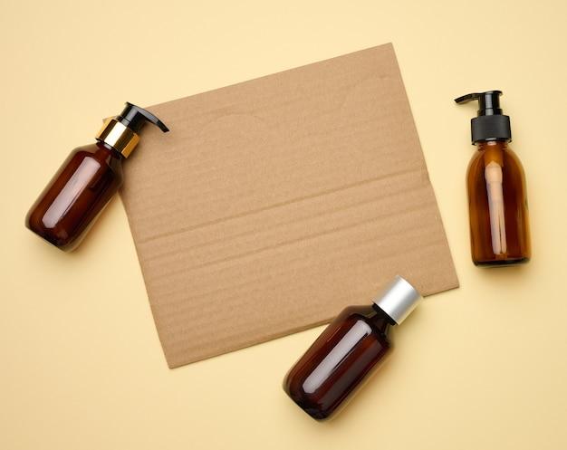 段ボール紙の空白の茶色のシートとディスペンサーベージュの背景を持つ茶色のガラス瓶。ジェル、美容液、広告、プロモーション用のパッケージ。天然有機製品。モックアップ