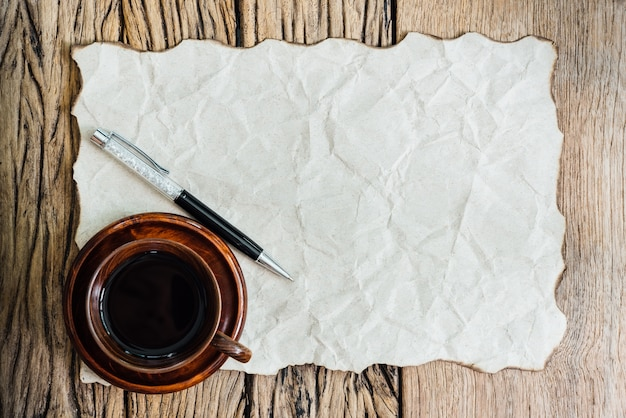 Blank burned paper with pen and coffee cup on old wood table.