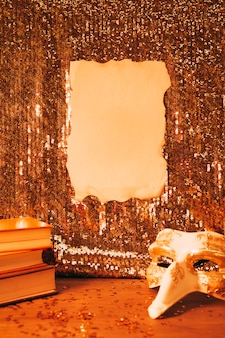 Blank burnt paper on shiny sequin fabric and party mask on desk