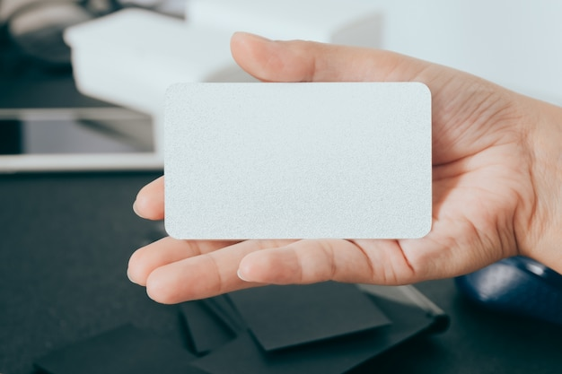 Blank business card in hand on blurred office desk background use us for mock up contact information design templet