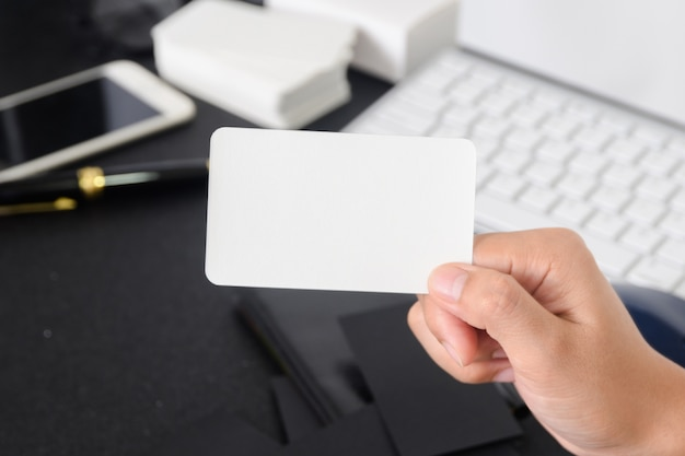 Blank business card mock up in hand on blurre office desk background use us contact information design templete