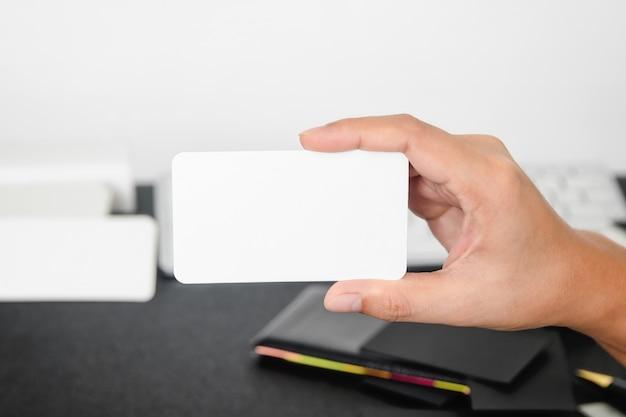 Пустая визитная карточка макет в руке на blurre офисный стол фон использовать нас контакт информация дизайн храм